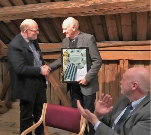 Leder i Vefsn lokalhistorie- og museumslag Hans Pedersen overrekker et diplom som bevis på æresmedlemsskapet til Svein Severinsen. Foran ordfører Jann-Arne Løvdahl.